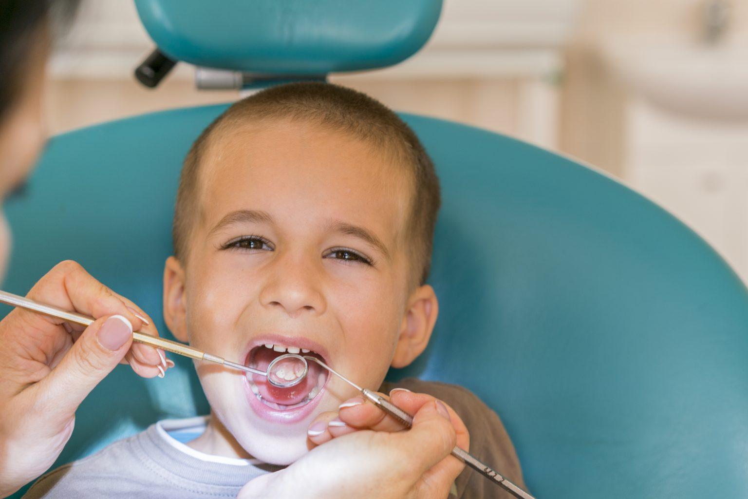 Pediatric Dentist Examining A Little Boys Teeth In The Dentists Chair At The Dental Clinic. Dentist Examining Little Boy's Teeth In Clinic