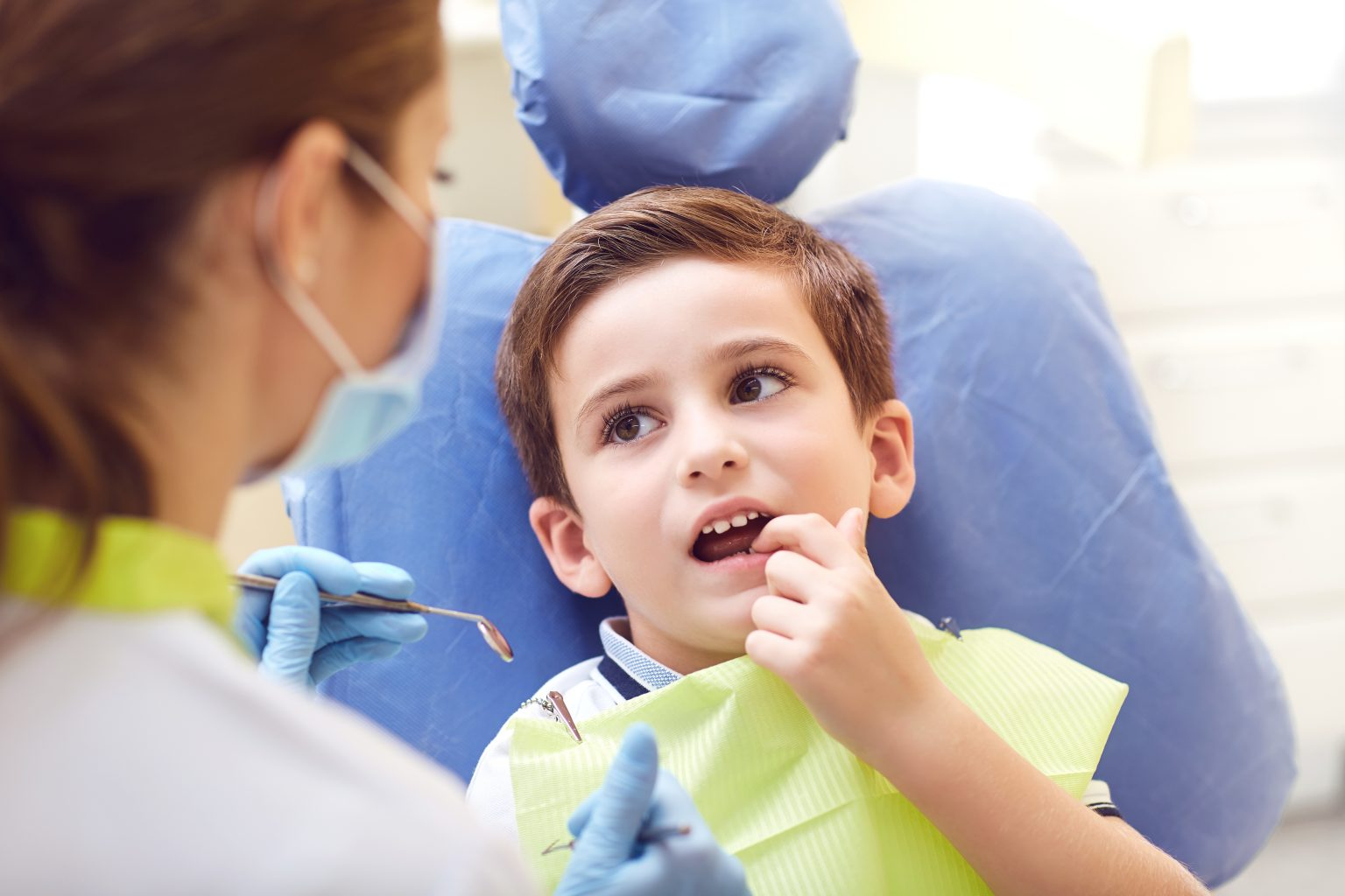 A Child With A Dentist In A Dental Office.